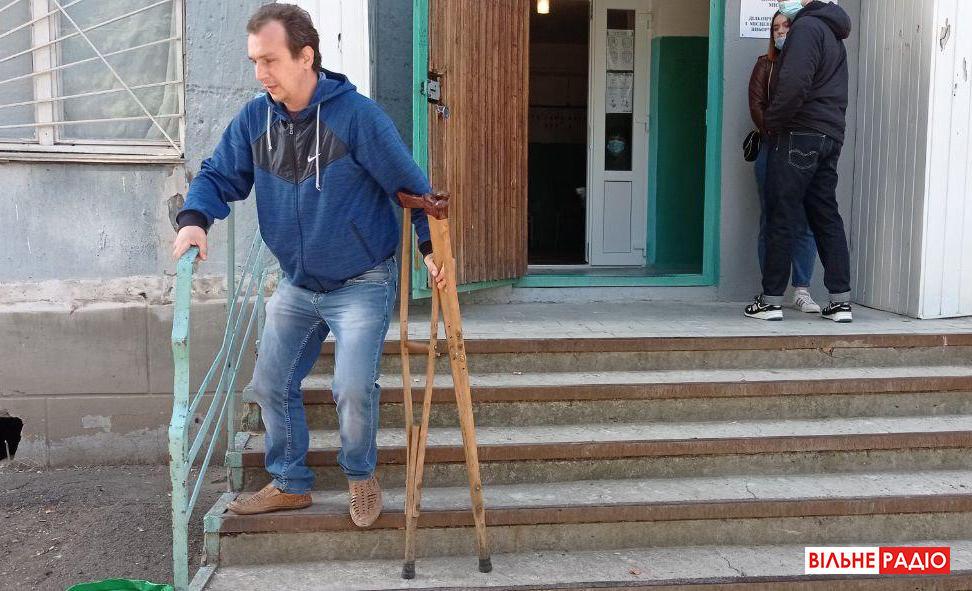 мужчина на костылях голосует маломобильный мужчина недоступный избирательный участок доступность инклюзия
