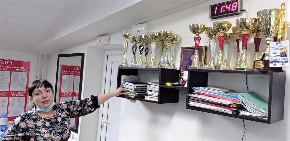 тренер по пауэрлифтингу Оксана Петренко возле командных кубков клуба