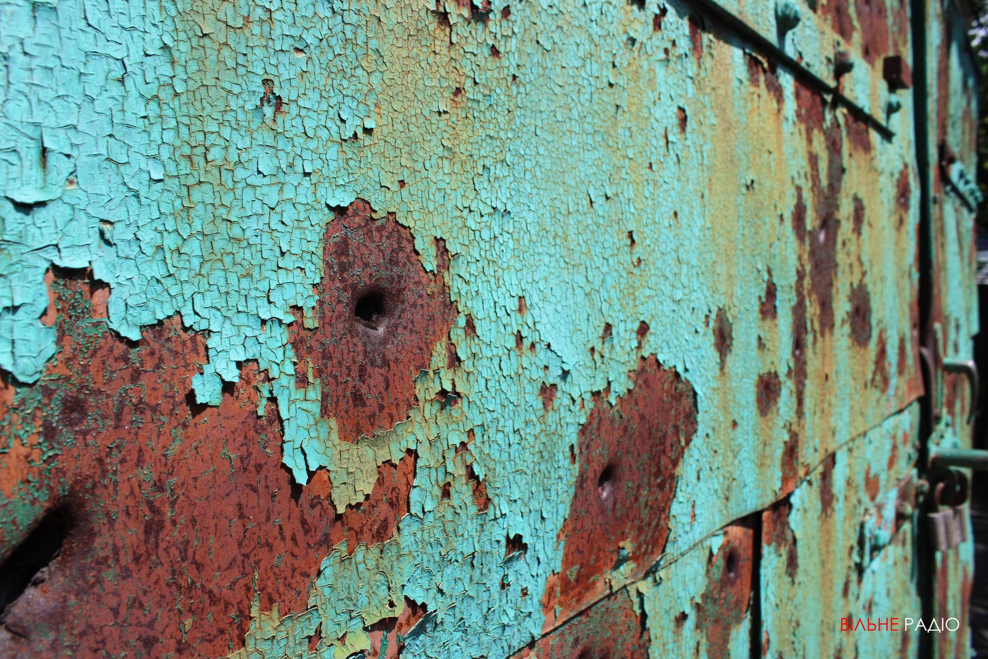 Двері гаража, пошкоджені обстрілами у Майорську
